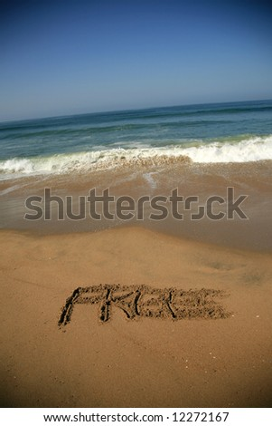 """Message says """"FREE""""  in the Sand on a Beach with waves and blue ocean concepts - stock photo"""