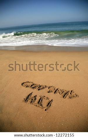 """Message says """"God says Hi""""  in the Sand on a Beach with waves and blue ocean concepts - stock photo"""