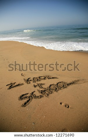 """Message says """"2 kool 4 school"""" in the Sand on a Beach with waves and blue ocean concepts - stock photo"""