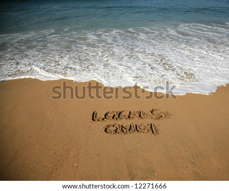 """Message says """"locals only""""  in the Sand on a Beach with waves and blue ocean concepts - stock photo"""