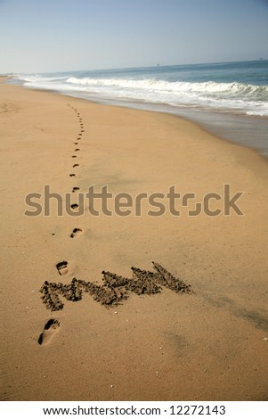 """Message says  """"MAN"""" in the Sand on a Beach with waves and blue ocean concepts  - stock photo"""