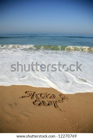 """Message says """"skools out"""" in the Sand on a Beach with waves and blue ocean concepts - stock photo"""