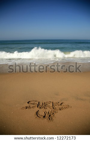"""Message says """"Surfs Up""""  in the Sand on a Beach with waves and blue ocean concepts - stock photo"""