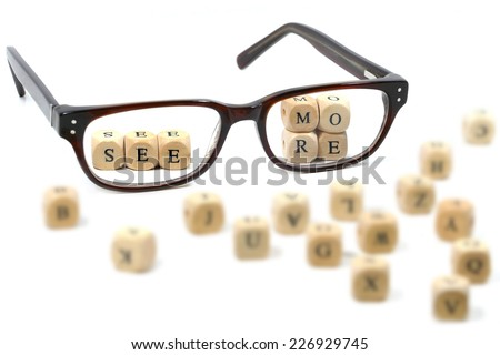 """message  """"see more"""" behind glasses, written in wooden blocks, isolated on white background, some blurry letters around, symbol, concept - stock photo"""