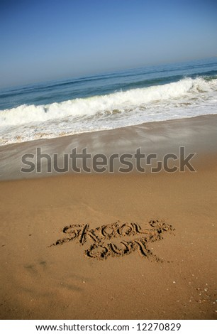 """Message """"skools out""""  in the Sand on a Beach with waves and blue ocean concepts - stock photo"""