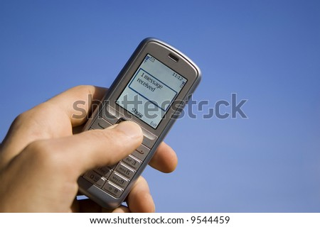 Message SMS received with mobile phone in the hand over blue sky
