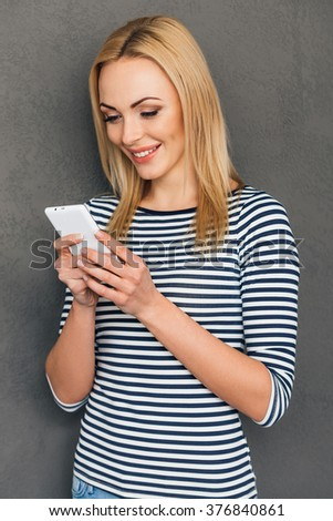 Message to friend.Beautiful young woman using her smart phone and looking at it with smile while standing against grey background - stock photo