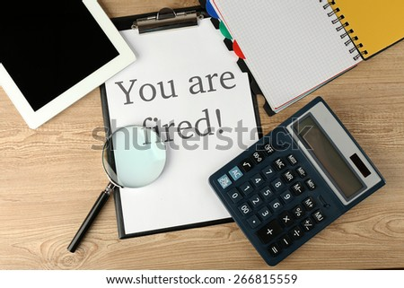 Message You're Fired on clapboard on wooden table, top view - stock photo