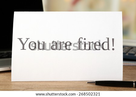 Message You're Fired on wooden table, closeup - stock photo