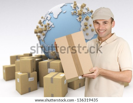 Messenger holding a package with a world map and cardboard boxes as a background - stock photo