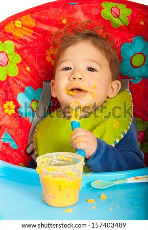Messy baby eating puree with spoon by yourself and sitting chair