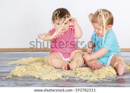 Messy baby toddlers having fun eating pasta - stock photo