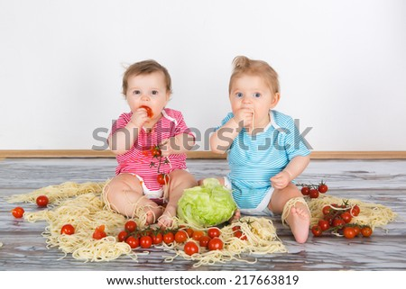 Messy baby toddlers having fun eating pasta and tomato - stock photo