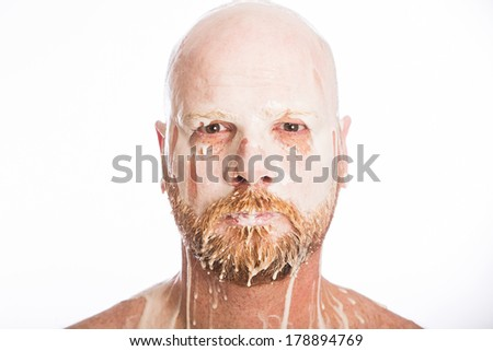 Messy bald man with milk on his face - stock photo