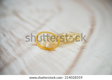 Messy bed in the hotel, condoms on the blanket. - stock photo