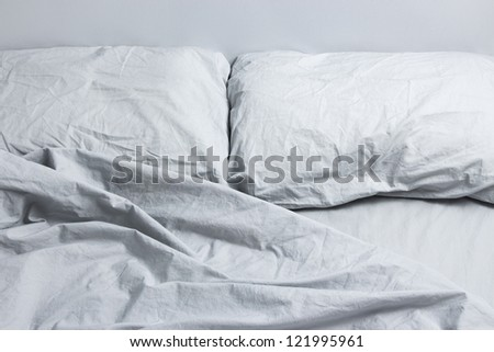 Messy bed with two pillows, gray bed linen. - stock photo