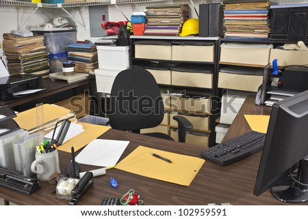 Messy, busy desk in a warehouse back office. - stock photo