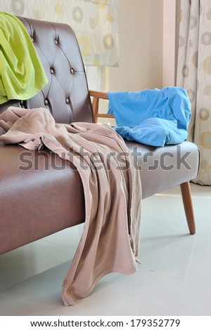 Messy clothes scattered on a leather sofa