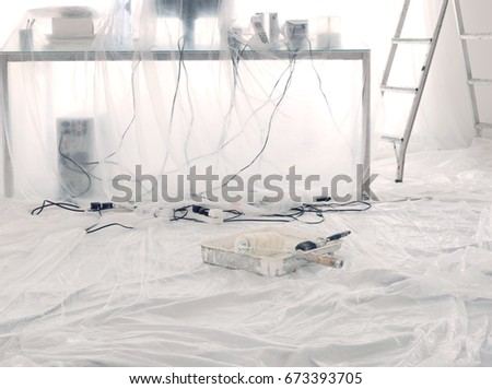 messy desk with computer and cables covered in dust sheets