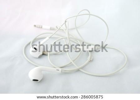 Messy earphones on white paper. - stock photo