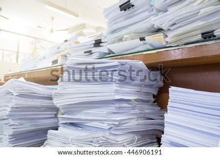 Messy office desk, Pile of unfinished paperwork - stock photo