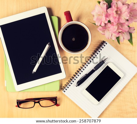 Messy office table with digital tablet, smartphone, reading glasses, notepad and cup of coffee. View from above with copy space - stock photo