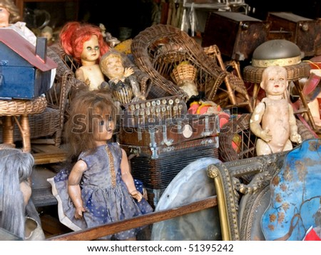 Messy packed room full of antique objects like dolls, an accordion, wicker or basket chairs - stock photo