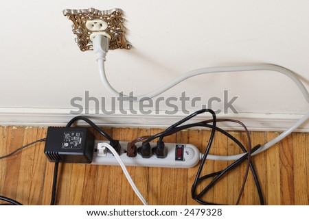 Messy power strip against wall plugged in