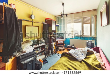 Messy room interior, a lot of different stuff, from electronic appliances and furniture to clothes.  - stock photo