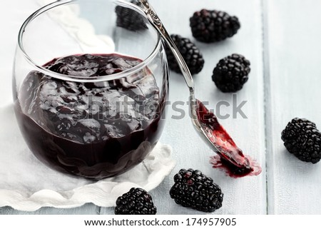 Messy spoon with blackberry jelly on a blue table. Extreme shallow depth of field and selective focus on jelly on spoon. - stock photo