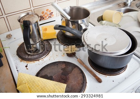 messy stove in domestic kitchen with grungy dishware, old pot and espresso maker, with dirty and used scrubber and yellow sponge  - stock photo