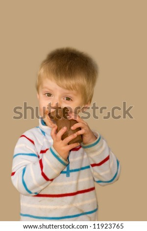 Messy toddler eating an easter egg. - stock photo