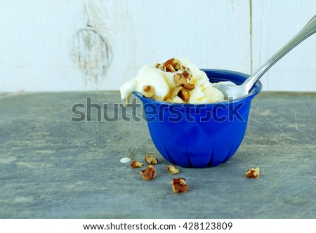 Messy vanilla ice cream with pecan chips melting in a blue, single serving size cup. A spoon rests in the ice cream. Rustic wood and steel background. Copy space. - stock photo