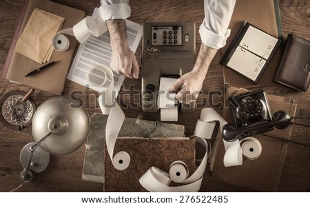 Messy vintage accountant's desktop with adding machine and paper rolls, he is working with the calculator - stock photo