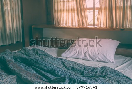 Messy white bed, Vintage filter. - stock photo