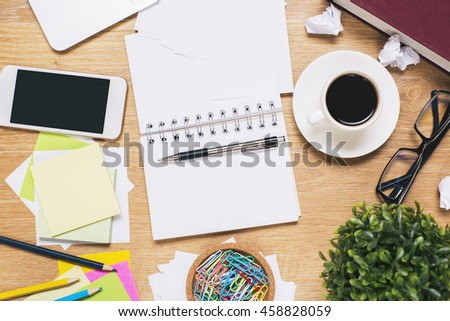 Messy workplace with blank smartphone, open spiral notepad, coffee cup, glasses, plant and various stationery items. Mock up