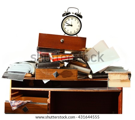 Messy workplace with stack of old paper and alarm clock