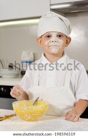 Messy young boy with flour on his face preparing to bake - stock photo