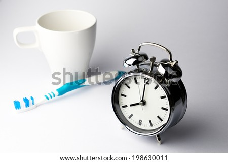Metal Alarm clock time with tooth brush on white background  - stock photo