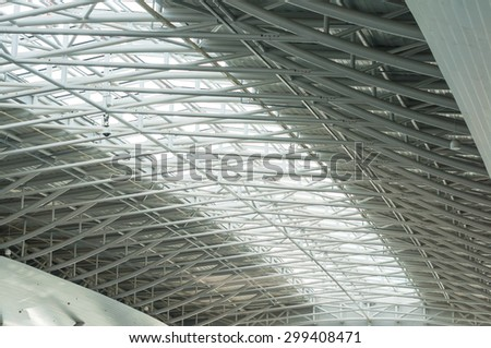metal and glass roof of a huge empty hangar.architecture detail.
