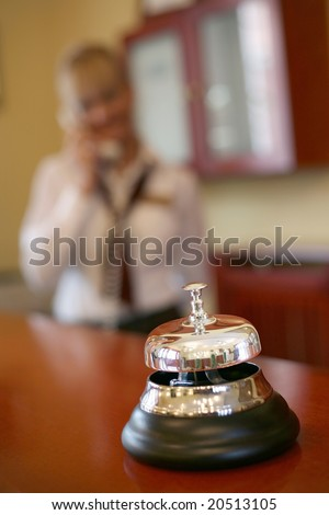 Metal and silver hotel bell, focus on the bell.Female receptionist in the background using a phone - stock photo