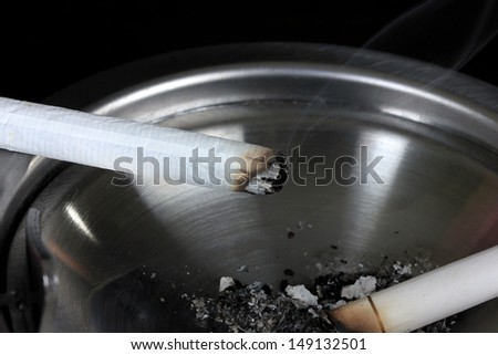 Metal  ashtray with cigarette, isolated on black