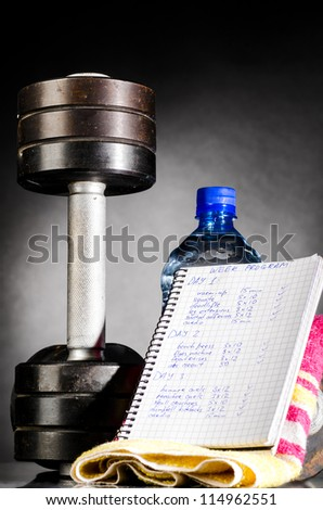 metal barbell with week program and water - stock photo