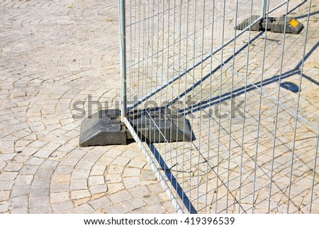 Metal barrier in a stone road  - stock photo