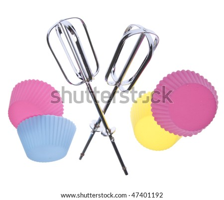 Metal beaters and cupcake tins in a fun pose for a cupcake party.  Isolated on white with a clipping path.