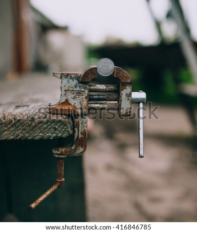 Metal bench vice with coin - stock photo