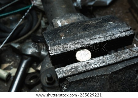 Metal bench vice with 1 euro coin - stock photo