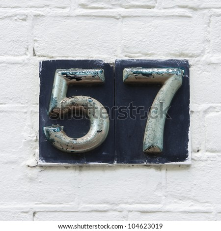 metal beveled house number fifty seven, painted over and flaking - stock photo