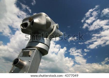 Metal binocluars with cloudy sky - stock photo