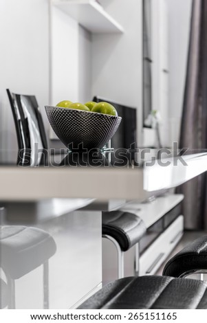 Metal bowl with fruits on kitchen glass table - stock photo